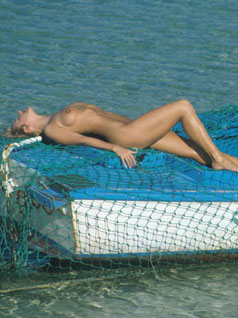 Naked woman laid on a boat in the sea